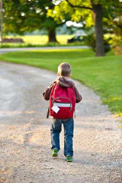 Foto de niño con mochila caminando por un parque